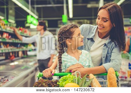 Family in the supermarket. Beautiful young mom and her little daughter are looking at each other and smiling in the background dad is choosing goods