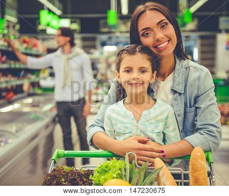 Family in the supermarket. Beautiful young mom and her little daughter are looking at camera and smiling in the background dad is choosing goods