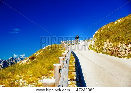 biker on mountain road, beautiful mountains in background