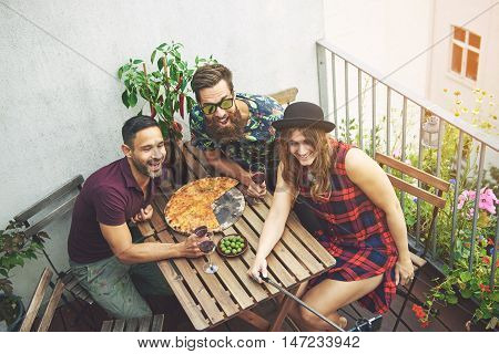 Woman in checkered dress takes photo with friends on patio while wearing black hat