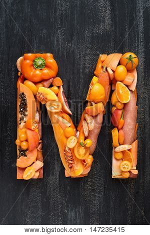 orange hued collection of  raw produce shaped to letters of alphabet, poster design element