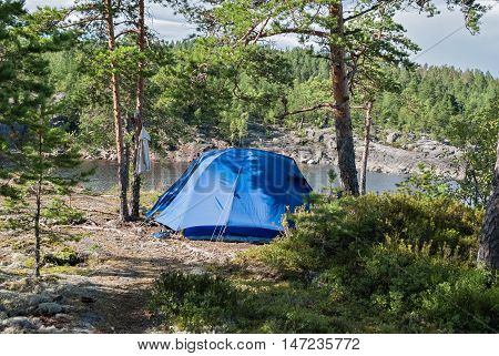 Blue tourist tent on the rocky shore of Lake Ladoga in Karelia.