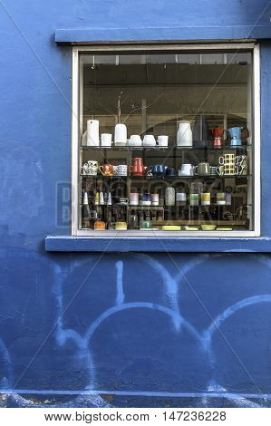 Window with shelves with assorted bric a brac set in a blue wall