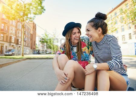Two trendy pretty young women sitting laughing and joking on a skateboard in a quiet urban street with copy space