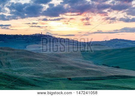 Tuscany rolling hills on sunset. Green fields and Pienza town in the background. Italy