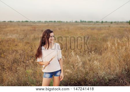 Young girl outdoors enjoying nature. Beauty teenage with long brown hair smiling and looks happily at the autumn meadow. Selective focus warm tinted.
