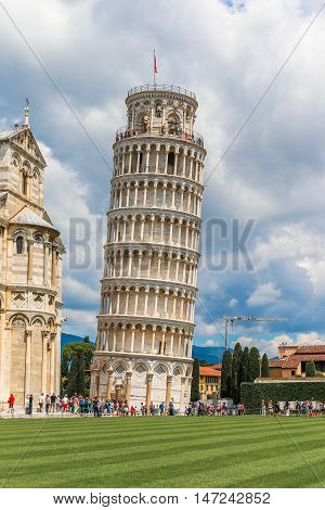 Pisa, Italy - May 1, 2016: Tourists visiting the Leaning Tower of Pisa and Pisa Cathedral in Italy. The Tower of Pisa is one of Italy's most iconic tourist attractions and is famous worldwide for its unintended tilt.