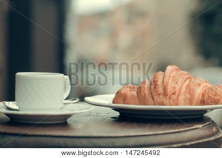 Fresh croissant and coffee cup on wooden table in cafe outdoors on streetscape background