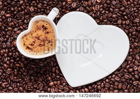 Hot beverage. White coffee cup heart shaped with cappucino latte on roasted beans background