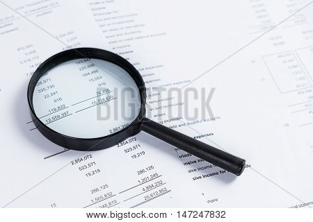 Magnifying glass on financial statement paper. Analyzing business financial data.