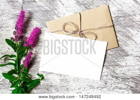Blank white greeting card and envelope with purple wildflowers on white rustic wood background with copy space for creative work design