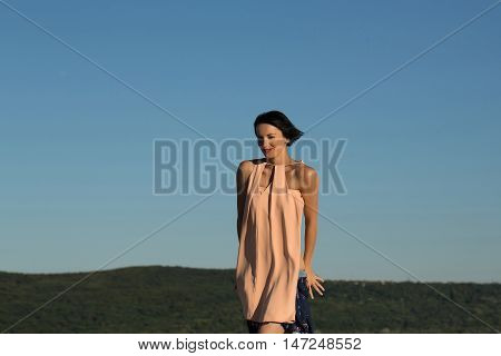 young sexy brunette woman with pretty face and short hair undressing sunny day on nature on blue sky background copy space
