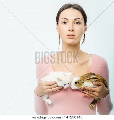 young woman or girl with pretty face in pink shirt holding little rabbit and kitten fluffy domestic animals pets isolated on white background copy space