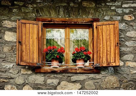 alpine stone facade with window shutters and red flowers