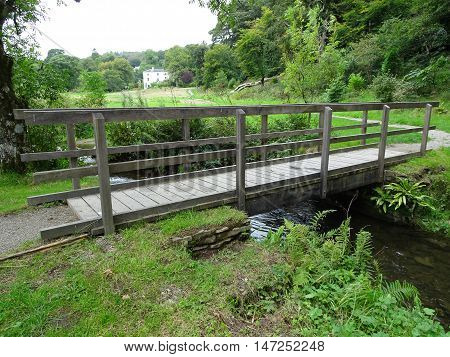 Bridge across river pathway and forest landscape photographed at Colby Woodland Garden near Amroth in Pembrokeshire