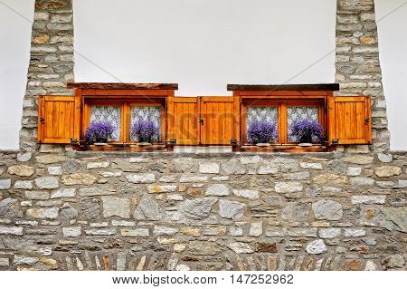 alpine building with two wooden windows and violet flowers