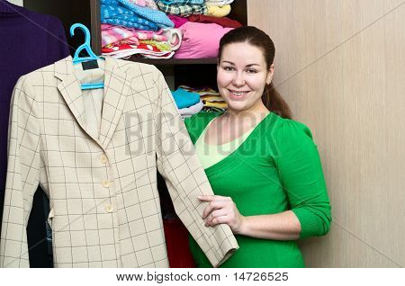 Young Caucasian Woman Holding A Suitcase And Standing Near The Wardrobe. Packing Things In A Shelves