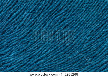 Blue background from a soft wool textile material closeup. Fabric with natural texture. Cloth backdrop.