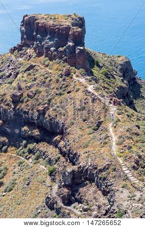 Exotic rocky path to the cliff rock on Santorini island. Sea on background