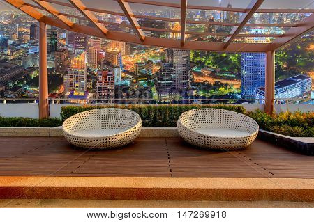 Relax corner on condominium rooftop garden with chairs on landmark bangkok top view at night background Landmark concept