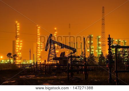 Group of oil rigs and wellhead at the background of refinery by night. Oil and gas industry.