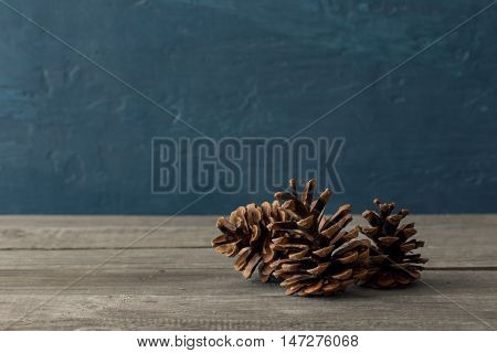 Three pine cones close-up on a wooden table with free place