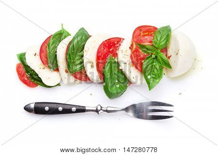 Caprese salad and fork. Mozzarella cheese, tomatoes and basil herb leaves. Isolated on white background. Top view