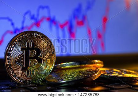 A golden bitcoin with keyboard and graph background. trading concept of crypto currency