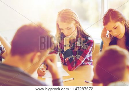 education, high school, learning and people concept - group of students with papers thinking or making test