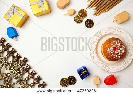 Hanukkah holiday background with menorah and sufganiyot on white background with copy space. View from above