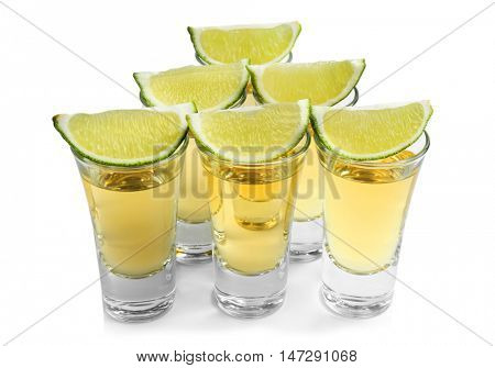 Shots of gold tequila with lime slices isolated on white