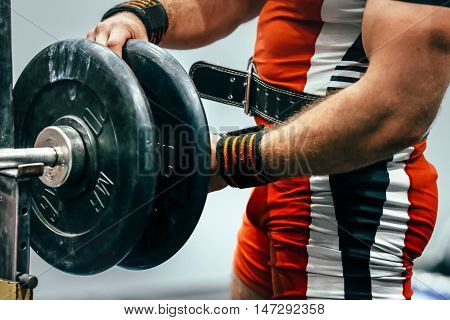 male athlete powerlifter preparing barbell for bench press in sport gym