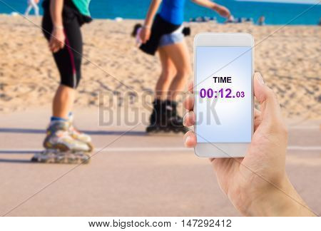 hand holding the smartphone with the chronometer function to measuring the time of the skaters race