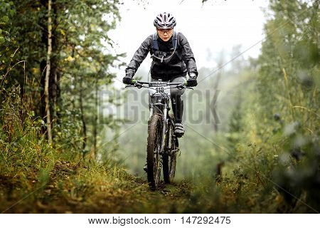 Revda Russia - July 31 2016: female athlete mountainbiker rides on forest trail during Regional competitions on cross-country bike