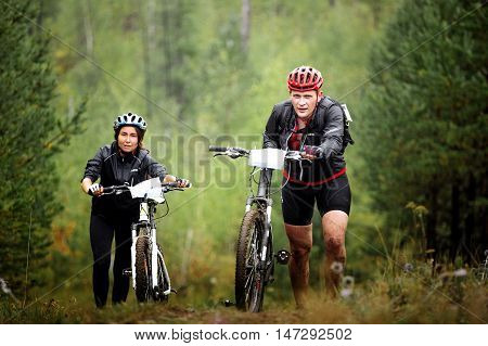 Revda Russia - July 31 2016: pair of male and female mountainbikers climb a steep hill in forest during Regional competitions on cross-country bike