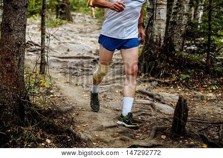 active man running mountain marathon in tree roots and rocks. knees in kneepads