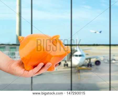 hand holding the piggy bank at the lounge airport