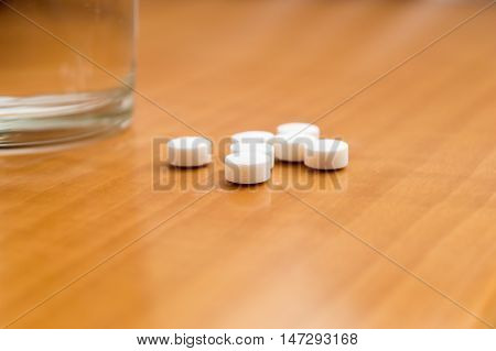 closeup of pills next to glass of mineral water over nightstand