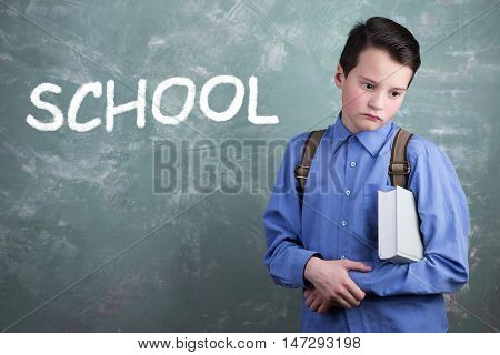 Schoolboy With Backpack And Book On The Background Of School Board With The Inscription