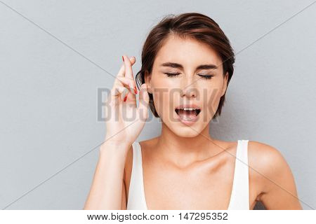 Tensed young woman standing with eyes closed and fingers crossed over gray background
