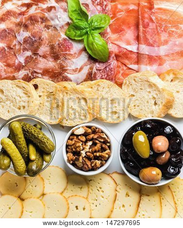 Meat and cheese snack set for wine. Prosciutto di Parma, salami, coppa, sliced bread, olives, nuts, pickles and cheese variety on white enamel background, top view
