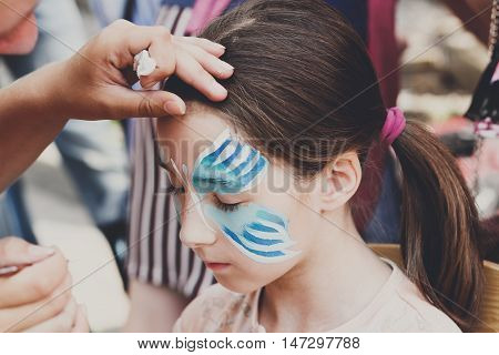 Child animator, artist's hand draws face painting to little girl. Child with funny face painting. Painter makes blue butterfly at girl's face. Children holiday, event, birthday party, entertainment.