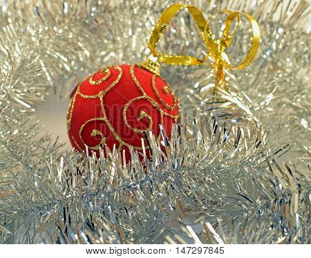 Red Christmas ball with silver tinsel. Closeup