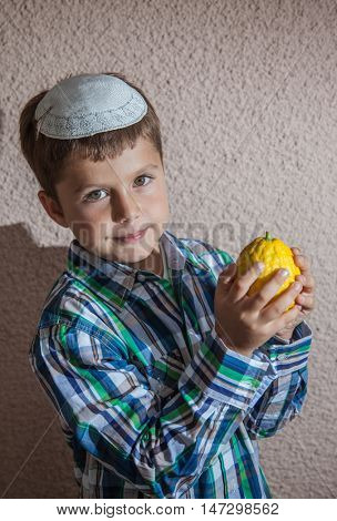 Very beautiful seven year old boy in white knitted kippah is holding citrus.  Etrog  -  ritual fruit for Sukkot
