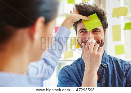 Sticky note on man's forehead during team training game in workshop