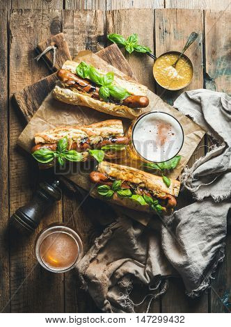 Glasses of wheat unfiltered beer and grilled sausage dogs in baguette with mustard, caramelised onion and herbs on serving board over rustic wooden background, top view, vertical composition