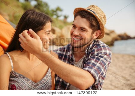 Young happy couple in love embracing while sitting at the tent at beach