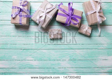 Many festive gift boxes with presents on turqoise wooden background. Selective focus. Place for text.