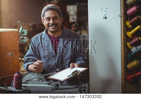 Portrait of smiling shoemaker holding clipboard and spectacle in workshop