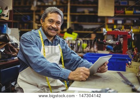 Portrait of shoemaker using digital tablet in workshop